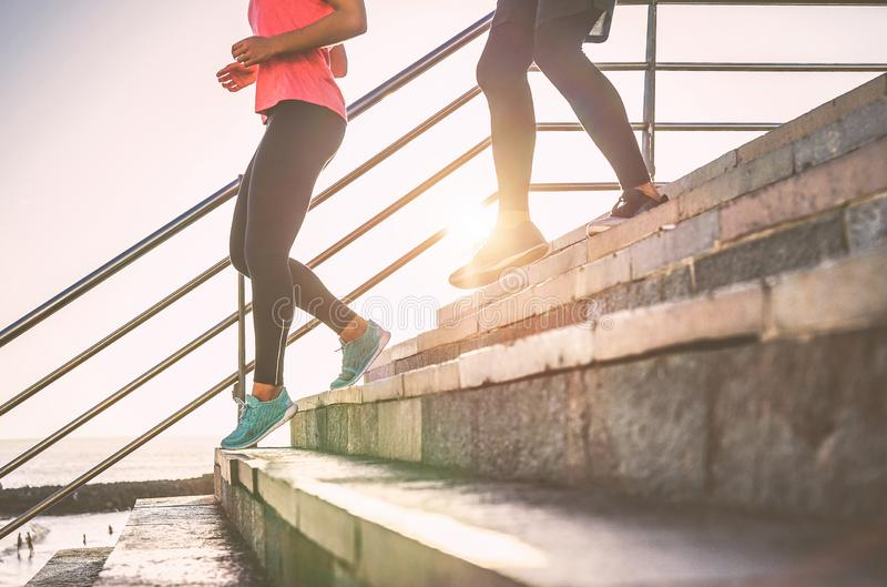 View of runners legs having a workout session on city stairs outdoor - Close up  of people running at sunset royalty free stock images