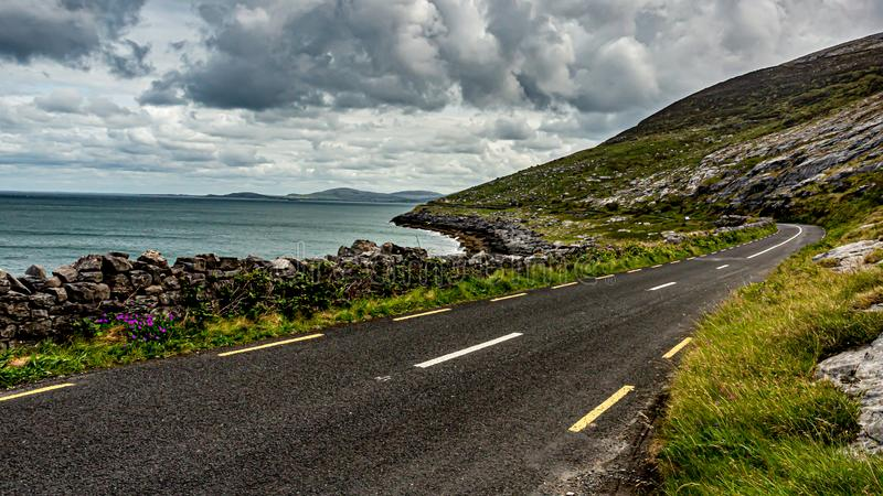 View of the rural coastal R477 road between the sea and the rocky area. Of ​​the Burren, geosite and geopark, Wild Atlantic Way, cloudy spring day stock image