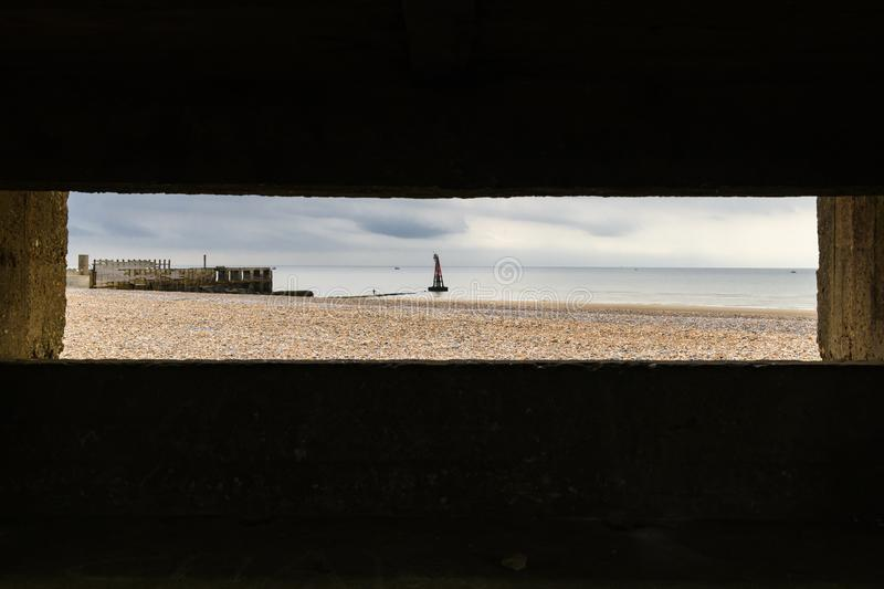 Pillbox view. The view of Rye beach from inside a world war 2 pillbox on the south coast of England. 30 August 2018 stock photography