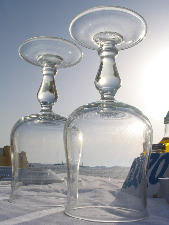 View of sailboat through wine glasses, Mykonos, Greece. View of a sailboat on the mediterranean through wine glasses on a seaside restaurant table, Mykonos stock photo