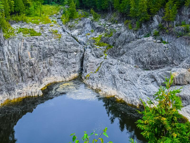 Water Leaking from a Crack in the Mountain. View of  the Saint John River  near the Grand Falls waterfall in New Brunswick, Canada, as water trickles through a stock photo