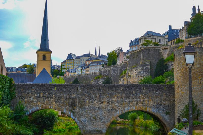 View of Saint Michael`s Church Eglise Saint-Michel in old town of Luxembourg City, Luxembourg, with an old stoned bridge and th royalty free stock photography