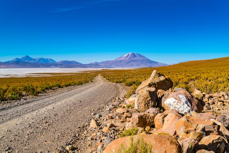 View of Salar de Uyuni with the dormant volcano and a dirty road royalty free stock photo