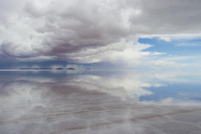 View of Salar De Uyuni Saltflats, water reflecting sky and mount. Flooded salt flat with sky and clouds reflected as a mirror, Salar De Uyuni, Bolivia stock images