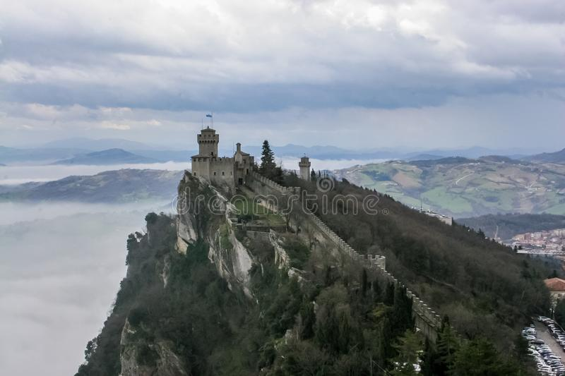 Castle on the mountain in clouds San Marino. View of San Marino castle in clouds and fog in springtime royalty free stock photos