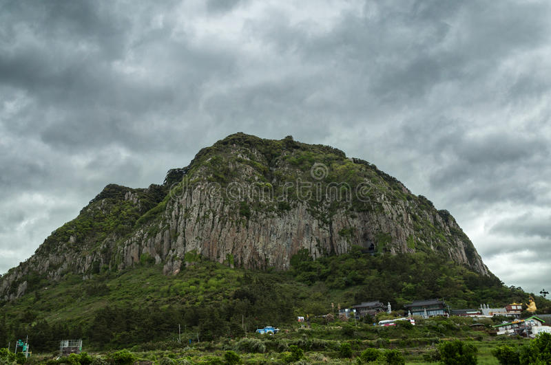 View of Sanbangsan Mountain on Jeju Island. View of volcanic Sanbangsan Mountain and a Buddhist temple below it on Jeju Island in South Korea at a gloomy and royalty free stock photography