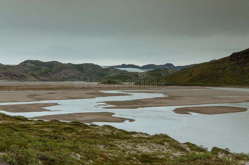 View through the Sandflugtdalen valley over river towards the mountains and Greenlandic icecap, Greenland stock photo