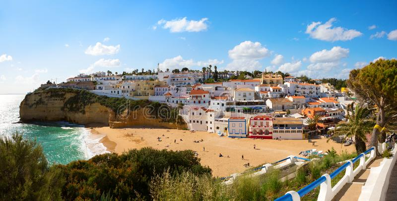 View of the sandy beach surrounded by typical white houses on a sunny spring day, Carvoeiro, Lagoa, Algarve, Portugal royalty free stock images