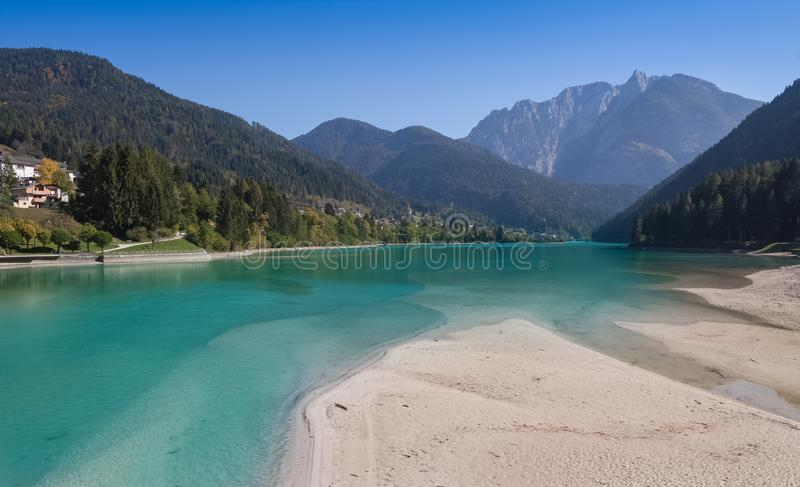 View from the sandy shore to the village Auronzo di Cadore the Lake Santa Caterina and the mountains dolomites in Italy. View from the sandy shore to the village stock images