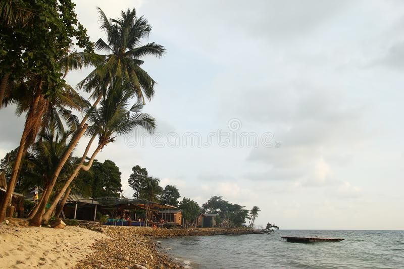 View on a sandy and stony beach with high palm trees and wooden houses near to the sea at sunset. Koh Chang, Thailand royalty free stock photos