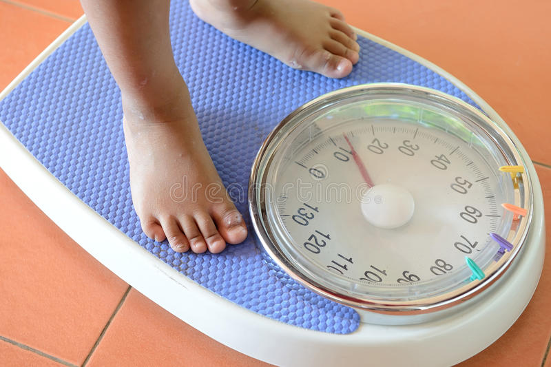 View of scales on a floor and kids feet stock photos