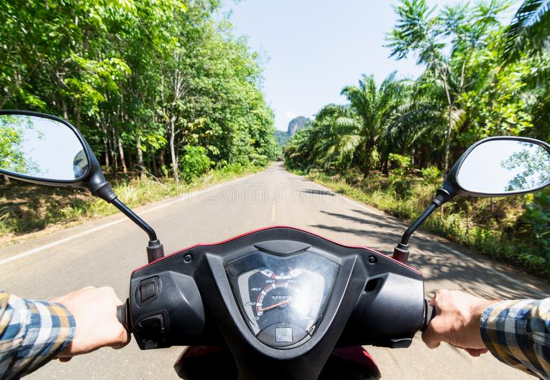 View from the scooter driver seat over the jungle road in Krabi province, Thailand royalty free stock images