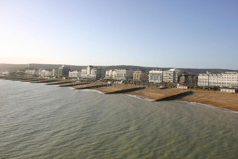 Eastbourne seafront. View of Eastbourne saefront with sea, beach, breakwaters (groynes) and tall buildings beyond with a blue sky stock photo