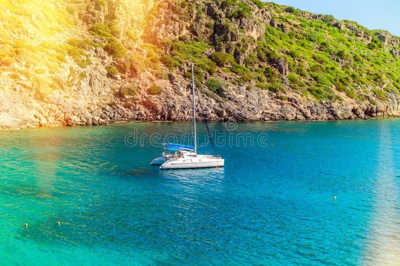 View of the sea and a catamaran near steep coast. View of the sea bay and a sailing catamaran near a steep coast of the island of Crete, Greece royalty free stock photo