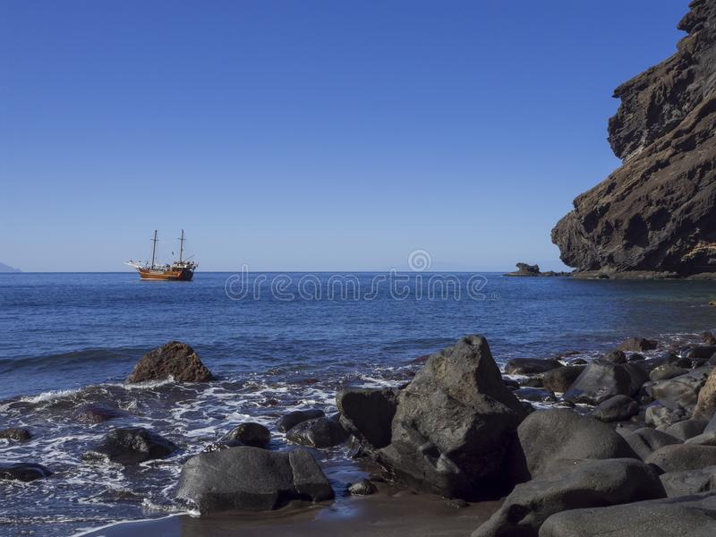View on sea horizon with old Sailing ship from black sand beach Playa De Masca. With big stones, cliffs and blue sky background stock image