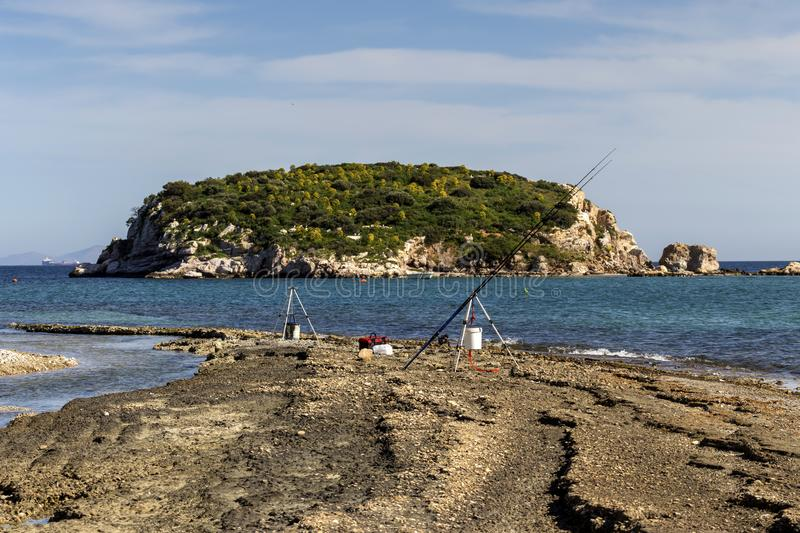 View of the sea and an islet in the distance and fishing rods royalty free stock photography