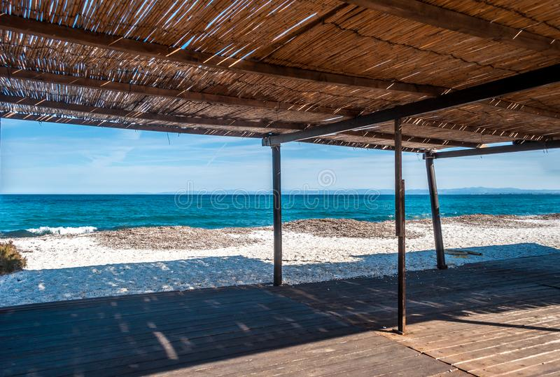 View of the sea from a reed gazebo. On the beach in summer, background, beautiful, blue, bungalow, cloud, color, grass, house, hut, landscape, nature, nobody stock photography