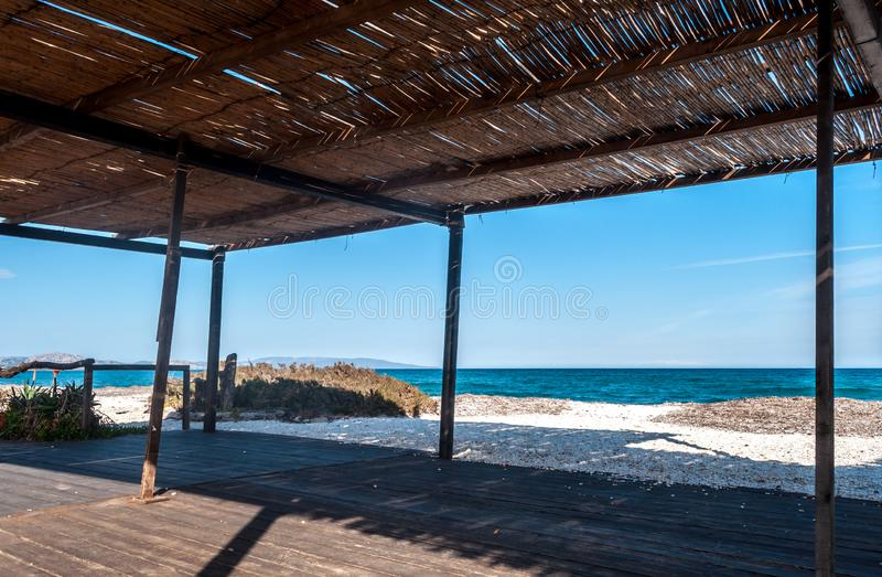 View of the sea from a reed gazebo. On the beach in summer, background, beautiful, blue, bungalow, cloud, color, grass, house, hut, landscape, nature, nobody royalty free stock image