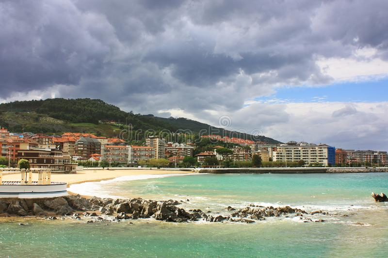 Castro urdiales beach. View of the sea shore against the backdrop of the city center on a sunny day. Storm clouds in the sky. Castro-Urdiales, Cantabria, North royalty free stock photo