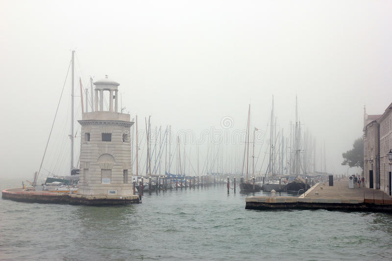 View from sea water on the old italian venetian boat dock with b. Oats in Venice misty morning royalty free stock photo