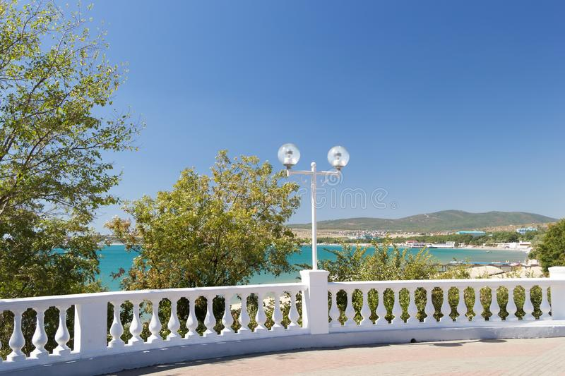 View on seascape through white stone balustrade from promenade on sunny day in Velvet season. Decorative balusters stock photography