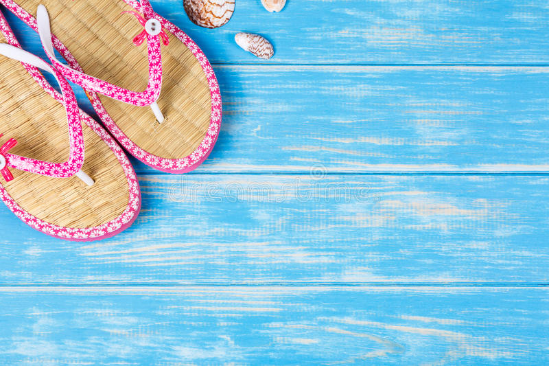 View of seashells and flip-flops lying on blue wooden background royalty free stock image