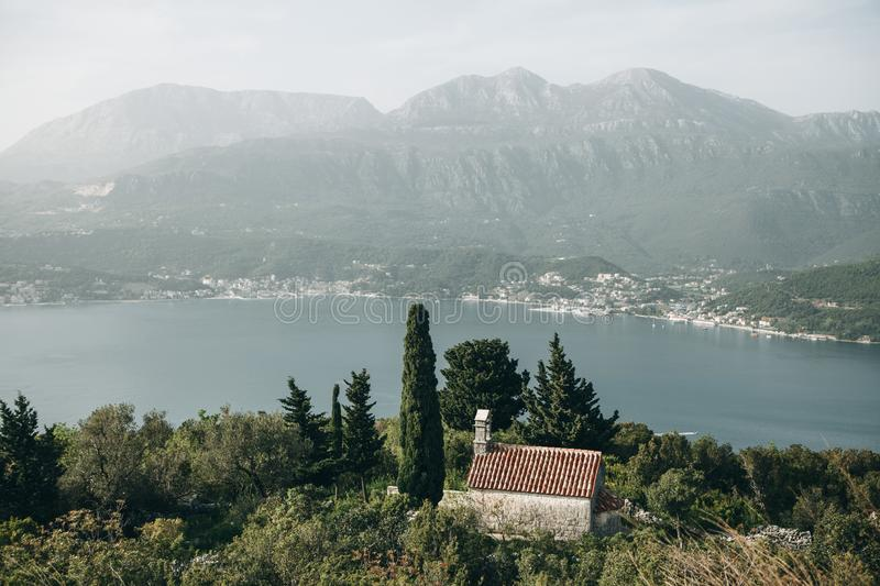 View of a secluded church. View of a secluded church among the trees by the sea in Montenegro stock photo