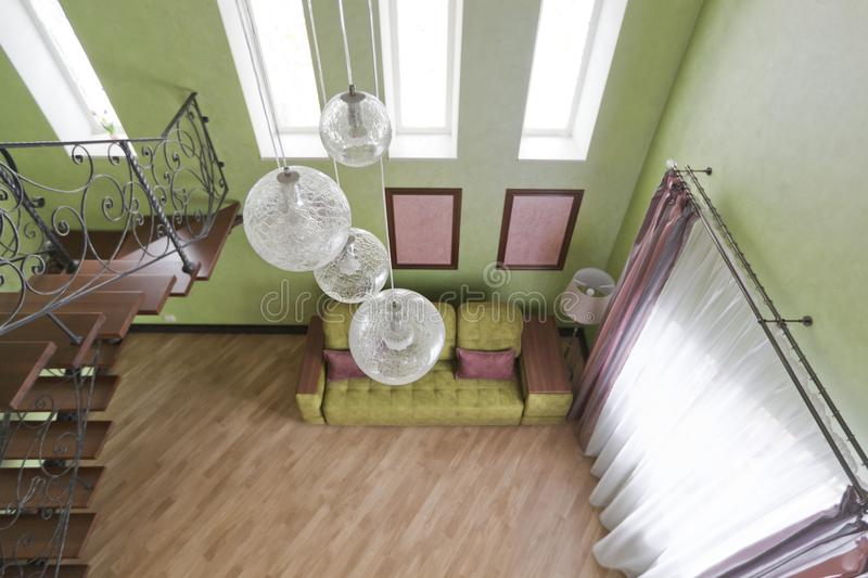 Interior in green and pink colors with green sofa and light parquet. View from the second floor to the first. Interior in green colors and a glass chandelier stock image