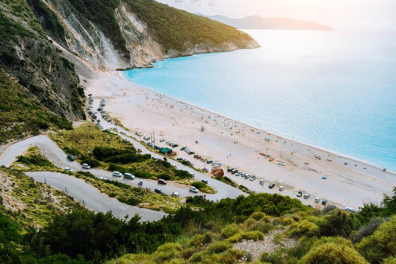 View of serpentine road lead to Famous Myrtos Beach, Kefalonia, Greece. Visiting amazing blue bay during cruise travel stock photo