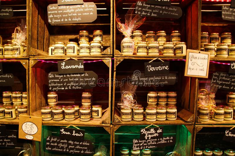 View on shelf made by wooden wine cases inside French shop with typical products. Glass jars with perfumed candles bougies prese. Roussillon Provence, France stock images