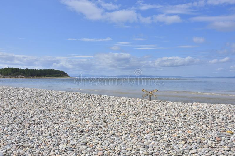 View from Shingle Beach in the North East of Scotland. View at low tide showing shingle beach and entrance to Findhorn Bay with the Culbin Forest on far side royalty free stock images