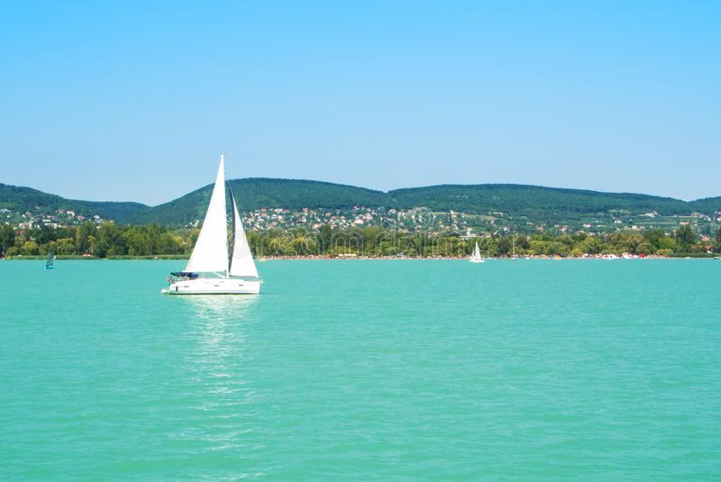 A view from a ship to bright Balaton lake water and a white yacht with a town, forest and mountains at the background on sunny royalty free stock photo