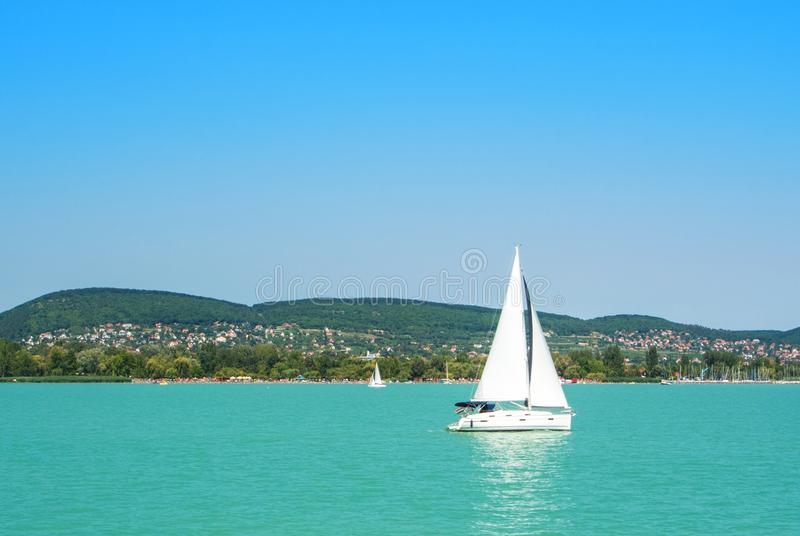 A view from a ship to bright Balaton lake water and a white yacht with a town, forest and mountains at the background on sunny stock image