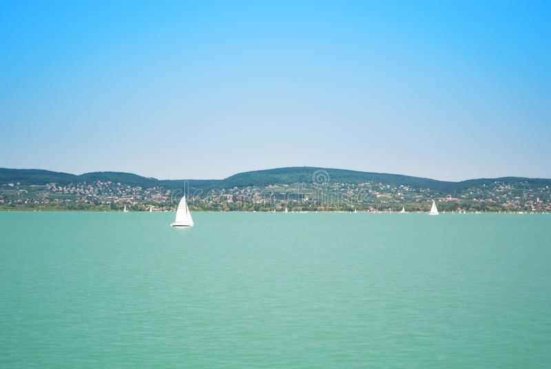 A view from a ship to bright Balaton lake water and a white yacht with a town, forest and mountains at the background on sunny stock photo