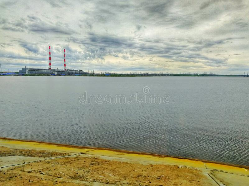The view from the shore of the reservoir to the water and gas power plant number two. Puffy clouds above it royalty free stock image