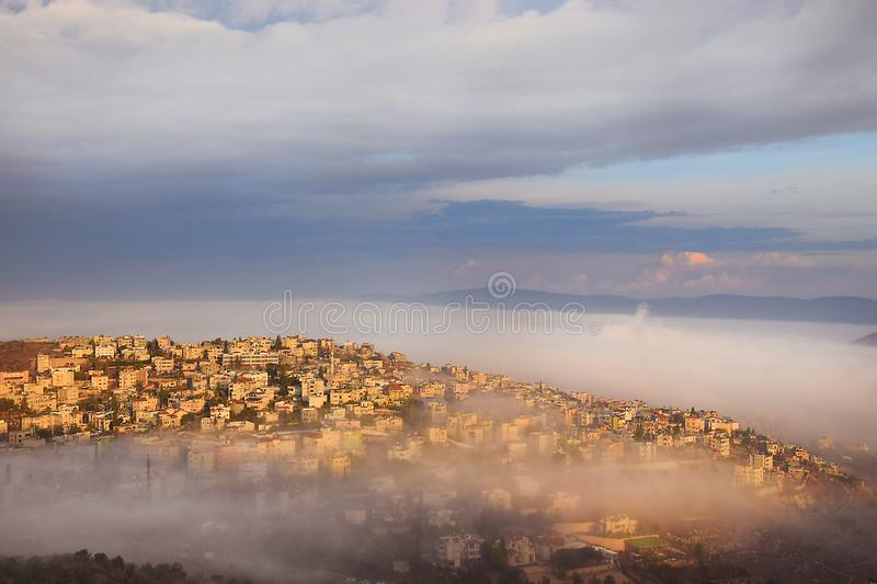 Biblical village Cana of Galilee  Kafr Kanna  in morning fog, Nazareth in Israel. View of the shrouded in the morning fog biblical village Cana of Galilee  Kafr stock images
