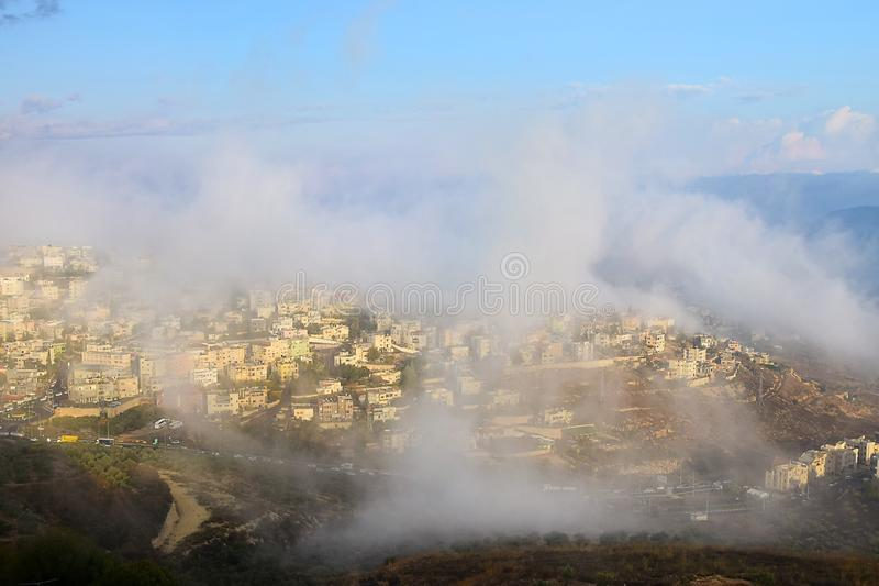 Biblical village Cana of Galilee  Kafr Kanna  in morning fog, Nazareth in Israel. View of the shrouded in the morning fog biblical village Cana of Galilee  Kafr stock photography