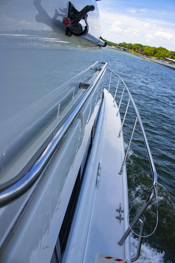 View from the side of a cabin cruiser on the lake with mirror reflection of the water and shore and a nearby marina stock photography