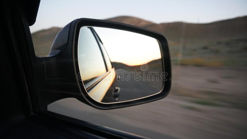 View in the side mirror of the car. Orange dawn beyond the hills. The car goes at speed. stock image