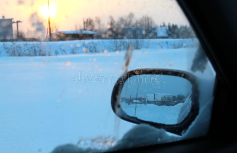 View from the side mirror of the car during the winter day. Side, car, mirror, weather, part, rear-view, closeup, white, snowstorm, snowbound, winter, cold, snow stock images