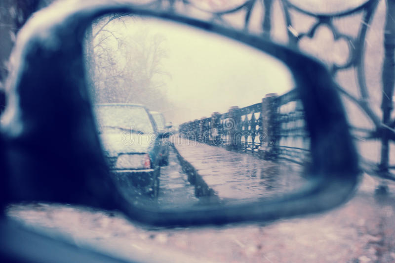 The view in the side rearview mirror of the car in inclement weather. View in the side rearview mirror of the car in inclement weather with flying snow in stock images