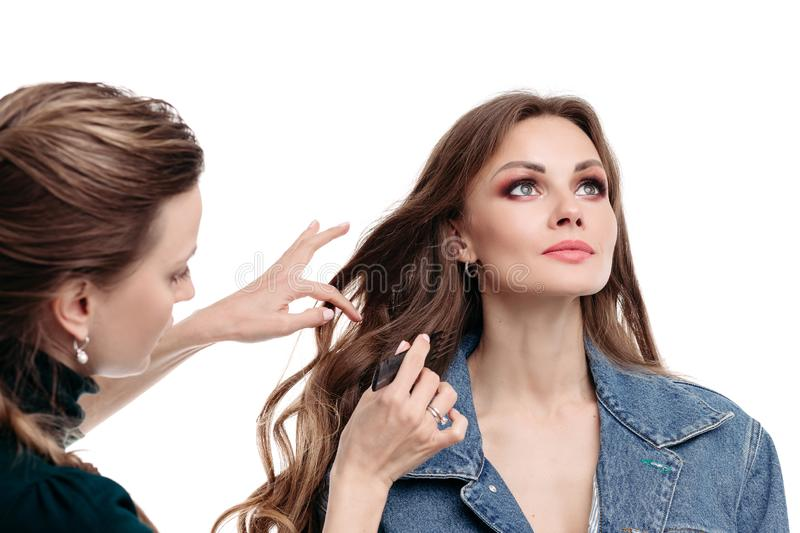 View from side of stylist doing hairstyle to model in studio royalty free stock photos