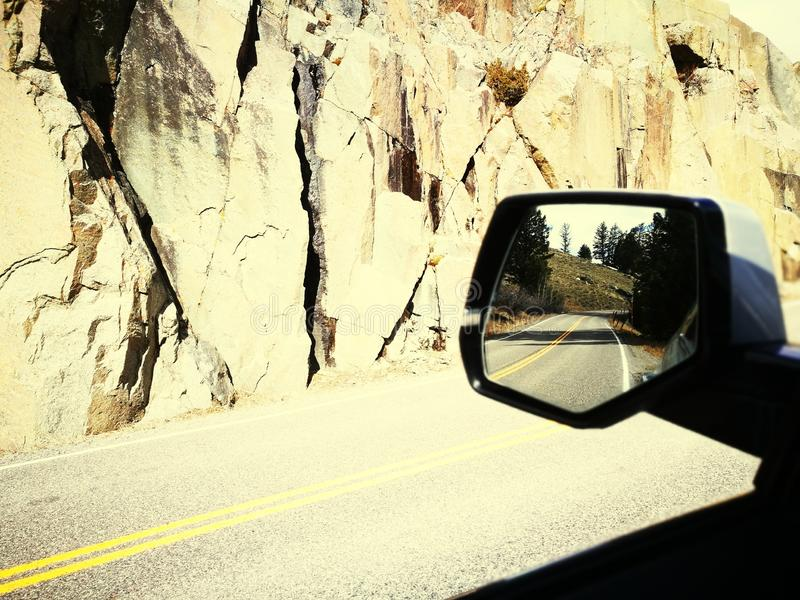 View into the sideview mirror while cruising through Yellowstone National Park stock image
