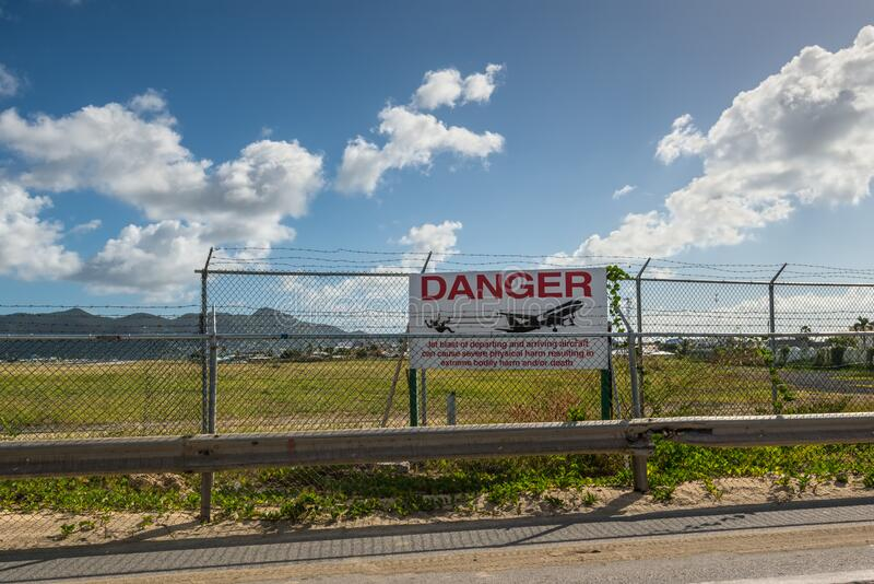 View of sign Danger near the Princess Juliana International Airport next to Maho Beach. Simpson bay, Saint Maarten - December 17, 2018: View of sign Danger near stock image