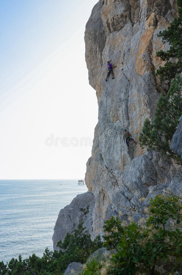 Rock climbers descend from the cliff at sunset. View of the silhouette of the cliff overlooking the sea, rock climbers climb the mountain at sunset royalty free stock image