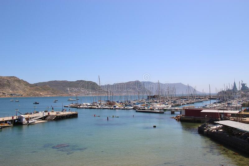 View of Simon`s Bay with town pier, marina and dockyard.  Simon`s Town, South Africa. Mountains of the Cape Peninsula in the background. Africa stock image