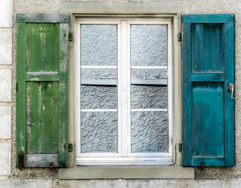 Single window with old blue and green wooden shutters royalty free stock photos