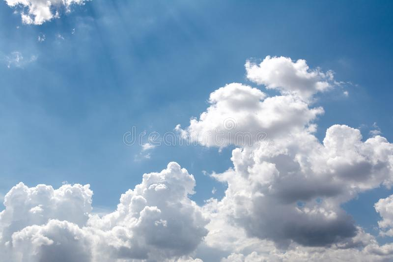 View of the sky of blue color and white clouds through which the sun`s rays make their way stock photo