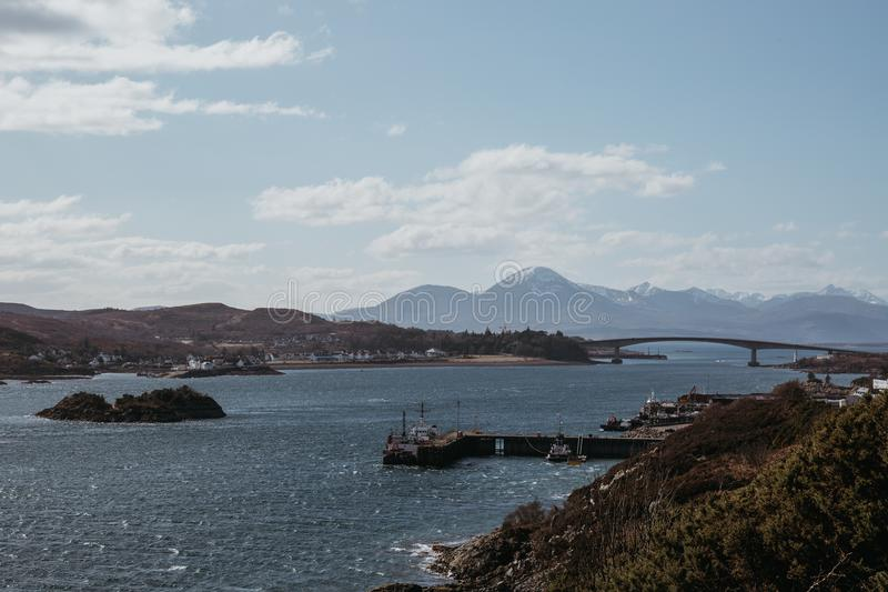 View of Skye Bridge and a small coastal village on Isle of Skye, Scotland, on a sunny day. View from Kyle of Lochalsh royalty free stock image