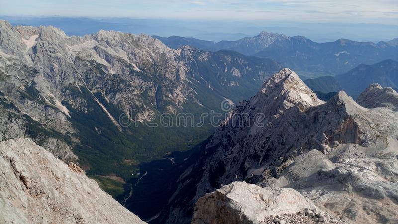 View on the Slovenian alps. Clear is blue with clouds. Under the mountain is deep valley with forests. Mountains are beautifuly white royalty free stock photos